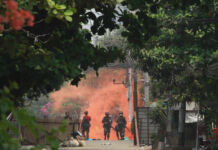 Soldiers in distance with reddish smoke behind them in area with trees and plants (© AP Images)