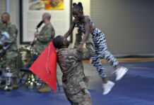 U.S. soldier lifting girl in air during celebration (U.S. Army/Staff Sergeant Paige Behringer)