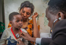 Doctor listening to child's heart with stethoscope as child sits on mother's lap (USAID/Riaz Jahanpour)