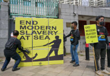 Men holding signs protesting slavery at sea (© Bay Ismoyo/AFP/Getty Images)