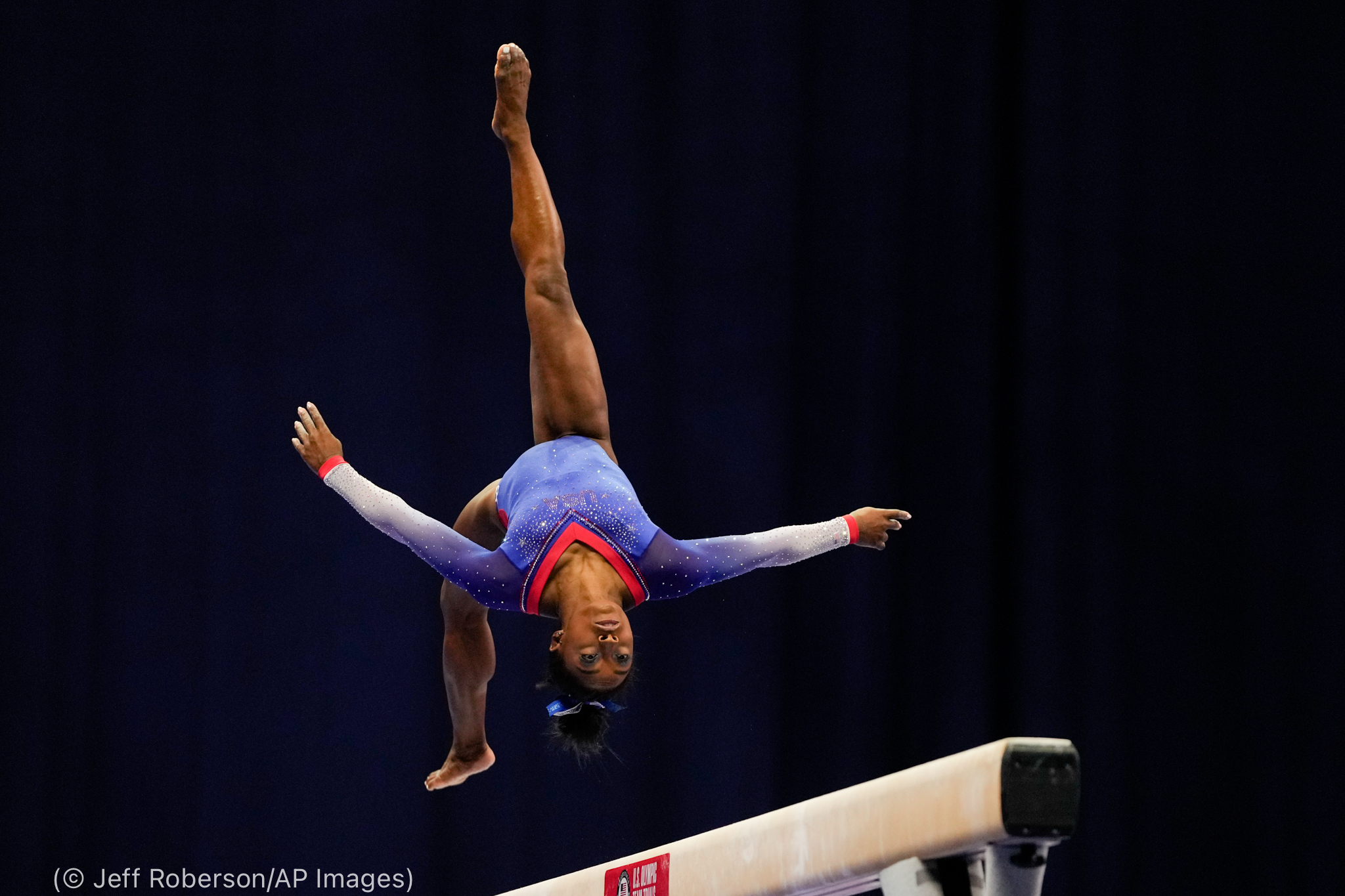 Simone Biles flipping in air over balance beam (© Jeff Roberson/AP Images)