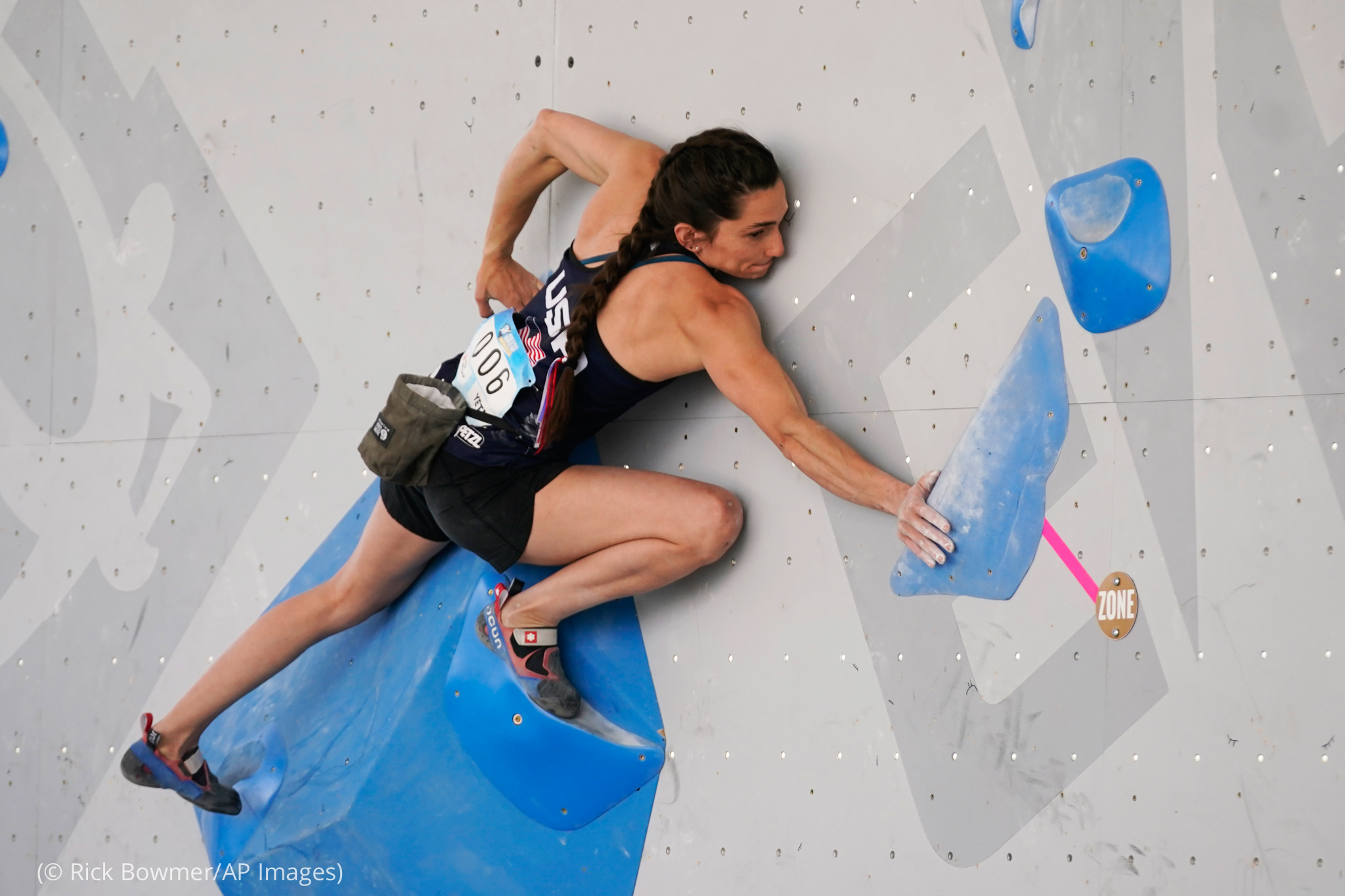Woman reaches for hold on climbing wall (© Rick Bowmer/AP Images)