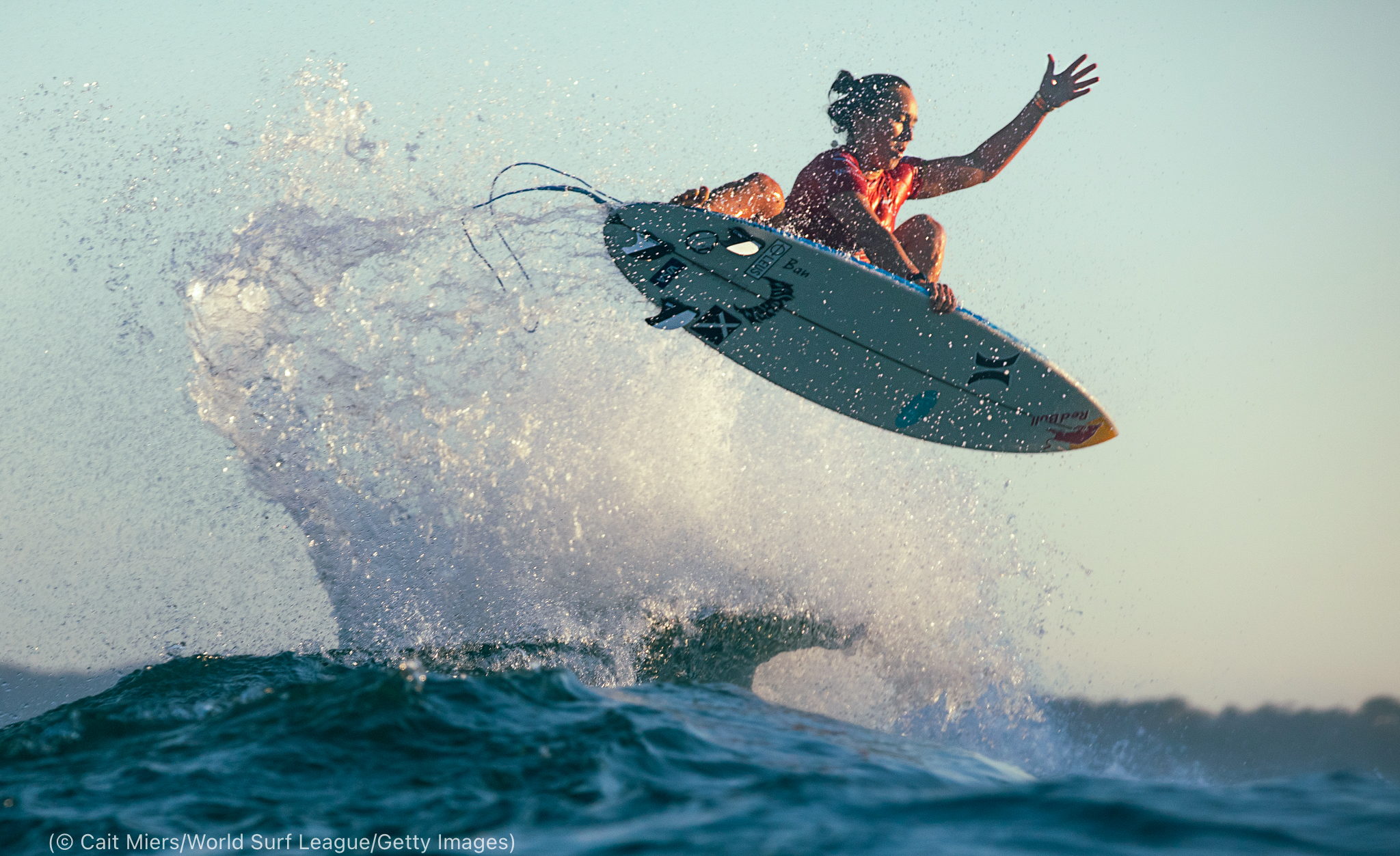 Woman flying over wave on surfboard (© Cait Miers/World Surf League/Getty Images)