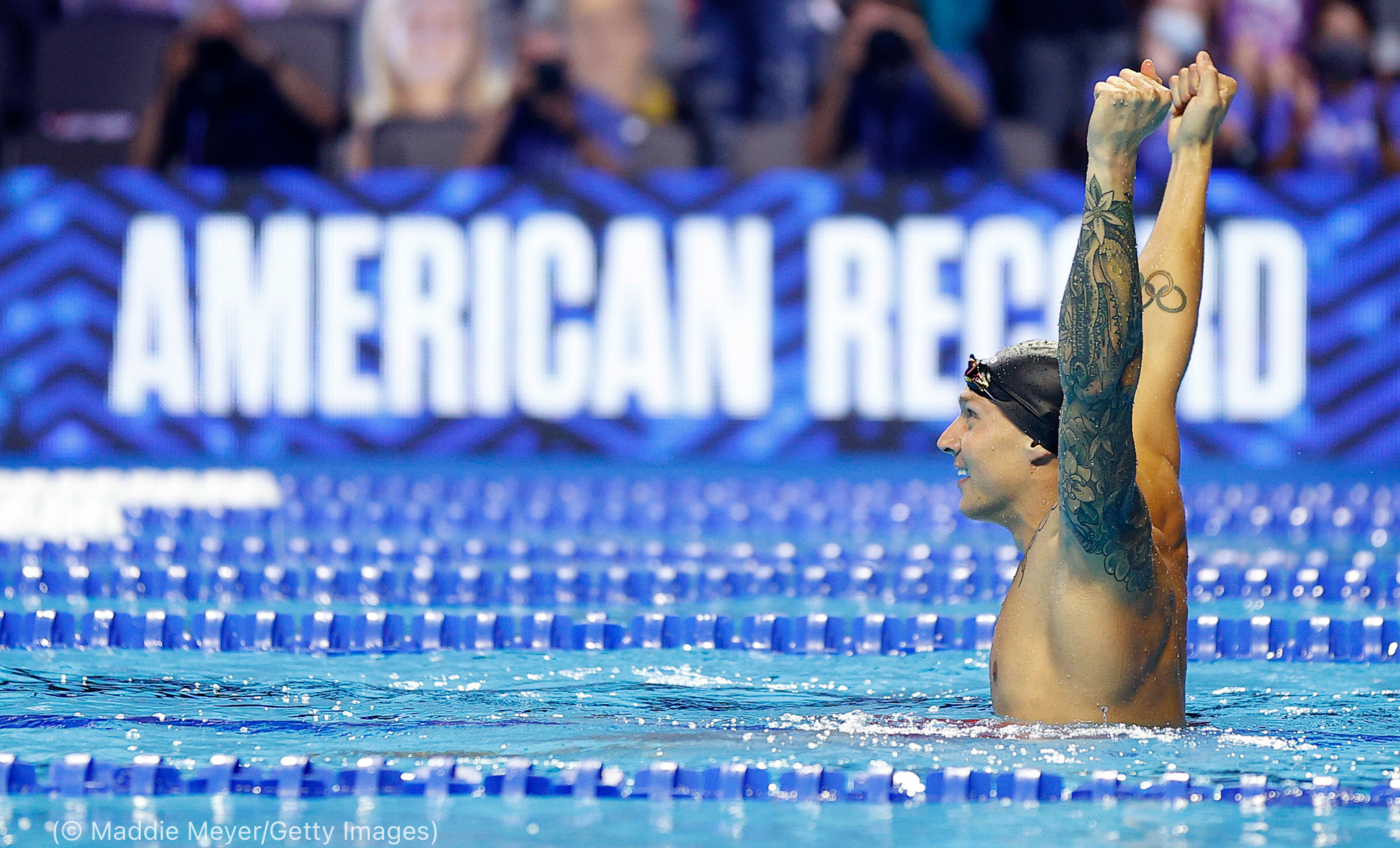 Male swimmer holding arms up in pool (© Maddie Meyer/Getty Images)